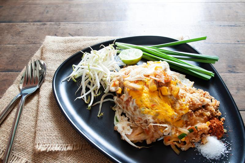 Pad Thai or stir-fried noodles with shrimp and egg on black plate. Thai food stock image