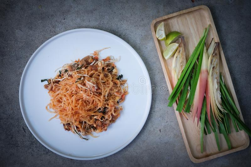 Pad Thai, stir-fried rice noodles in white plate with slide lemon and green vegetable royalty free stock photos