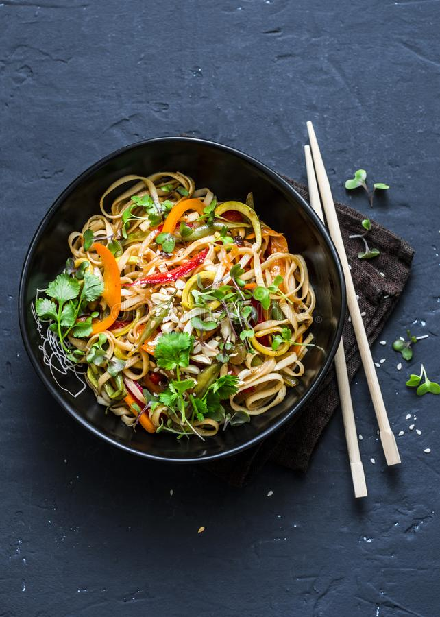 Pad Thai vegetarian vegetables udon noodles in a dark background, top view. Vegetarian food in asian style. Copy space stock photo