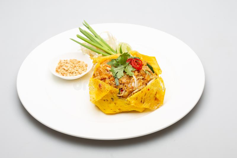 Pad Thai and wrapped in egg.thai food. Pad Thai, egg wrapped on a white plate and a white backdrop royalty free stock photography