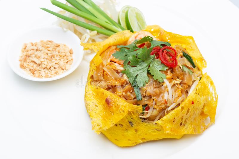 Pad Thai and wrapped in egg.thai food. Pad Thai, egg wrapped on a white plate and a white backdrop stock image
