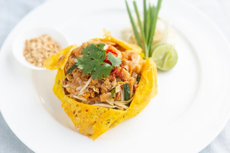 Pad Thai and wrapped in egg.thai food. Pad Thai, egg wrapped on a white plate and a white backdrop stock images