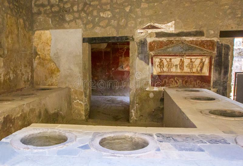 A padaria da bancada em Herculaneum com as cubas da argila construídas no forno, que serviu como cremalheiras para o comércio de  imagens de stock royalty free