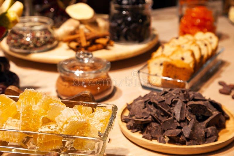 Padaria do close up e petiscos, frutos secados, partes queijo parmesão, favos de mel, chocolate escuro, varas de canela, biscotti fotografia de stock