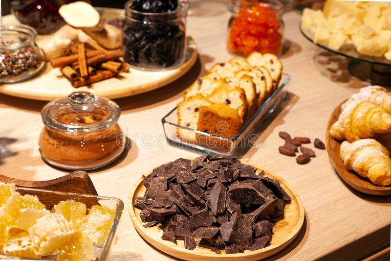 Padaria do close up e petiscos, frutos secados, partes queijo parmesão, favos de mel, chocolate escuro, varas de canela, biscotti imagens de stock