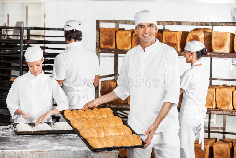 Padaria masculina segura de Showing Breads In do padeiro imagem de stock royalty free