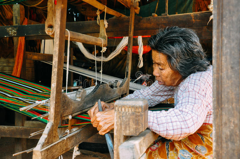 A Padaung elder working a loom at Inle Lake. stock images