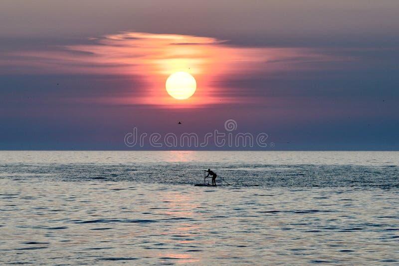 Paddel-Internatsschüler unter einem aufgehende Sonne auf Michigansee #1 lizenzfreies stockbild