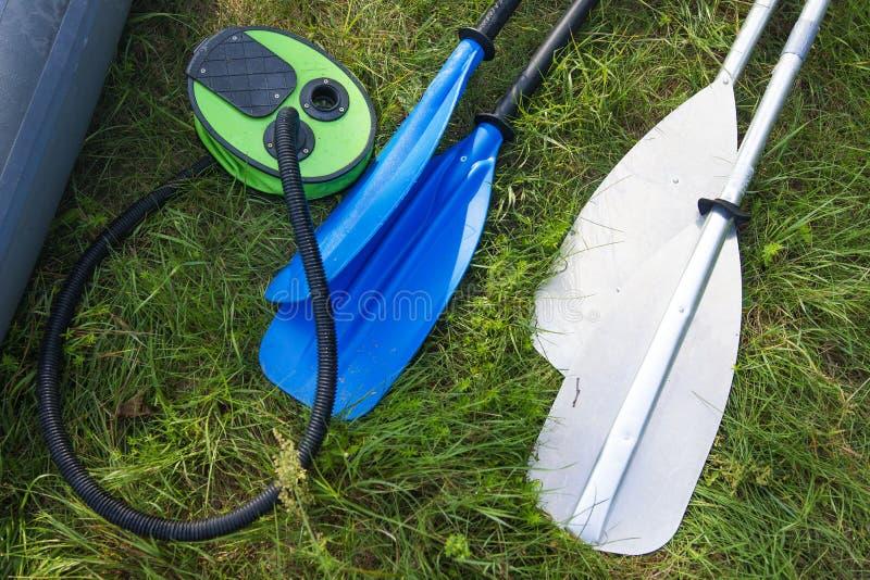 Paddel und Pumpe für Kajaks auf der Flussbank Ruder für ein Boot, ein Kanu oder einen Kajak stockbild