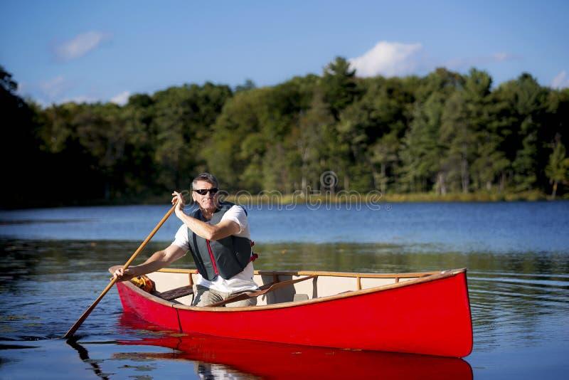 Paddelend een Rode Kano - Canada stock afbeeldingen