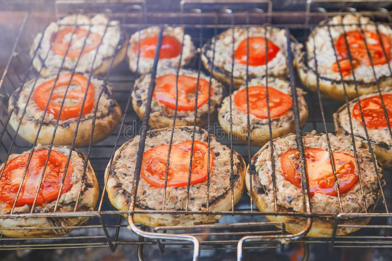 Paddestoelen met tomaten op de grill worden geroosterd die royalty-vrije stock foto's