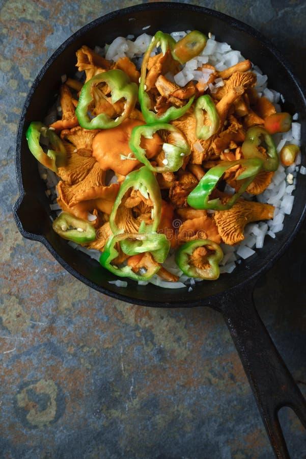 Paddestoelencantharellen, uien en peper in een pan royalty-vrije stock foto's