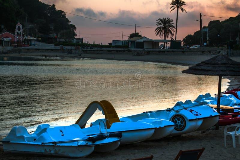 Paddle łodzie jeden z obruszeniem Stacjonują wzdłuż linii brzegowej Założenia i drzewa na tle Różowawy Szary niebo obrazy stock