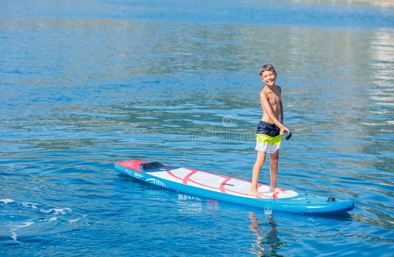 Paddle boarder. Child boy paddling on stand up paddleboard. Healthy lifestyle. Water sport, SUP surfing tour royalty free stock images