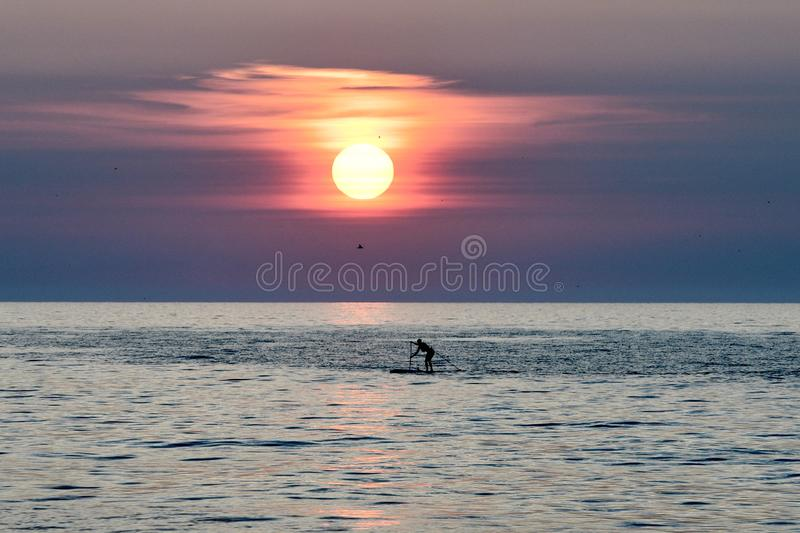 Paddle Boarder Under A Rising Sun on Lake Michigan #1. This is a Summer picture of a paddle boarder under a rising sun on Lake Michigan off Diversey Harbor royalty free stock image