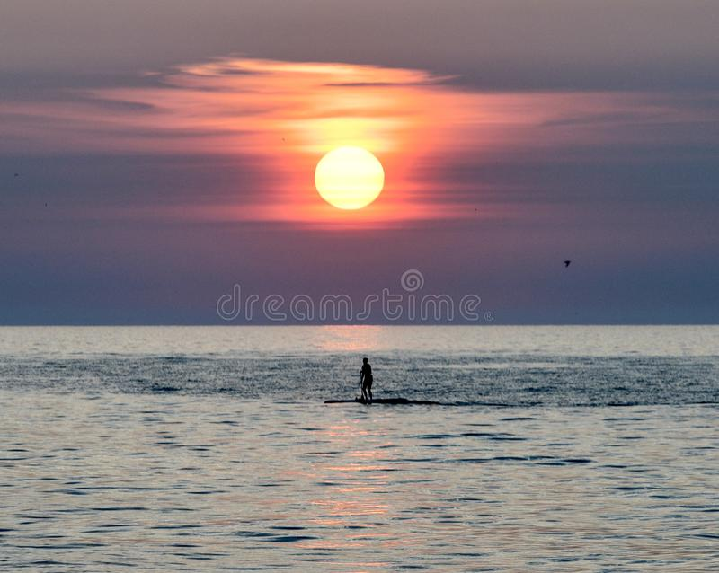 Paddle Boarder Under A Rising Sun on Lake Michigan #2. This is a Summer picture of a paddle boarder under a rising sun on Lake Michigan off Diversey Harbor royalty free stock image