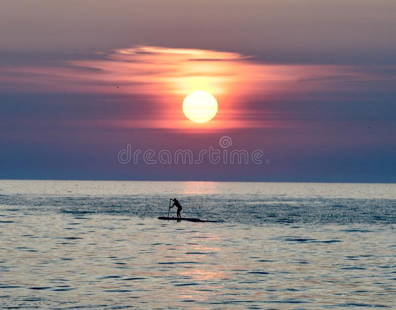 Paddle Boarder Under A Rising Sun on Lake Michigan  3. This is a Summer picture of a paddle boarder under a rising sun on Lake Michigan off Diversey Harbor royalty free stock photo