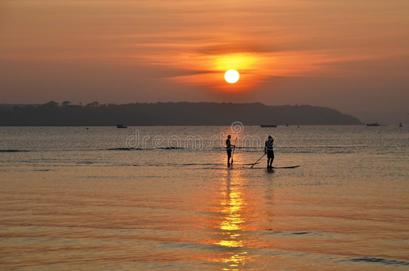 Paddle boarding at sunset stock photos