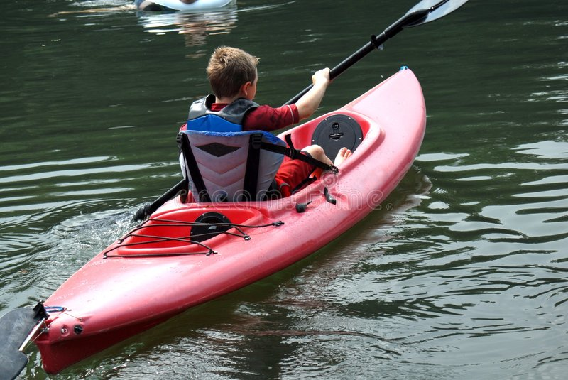 Paddle the Boat. Young boy on the lake paddling a boat royalty free stock image