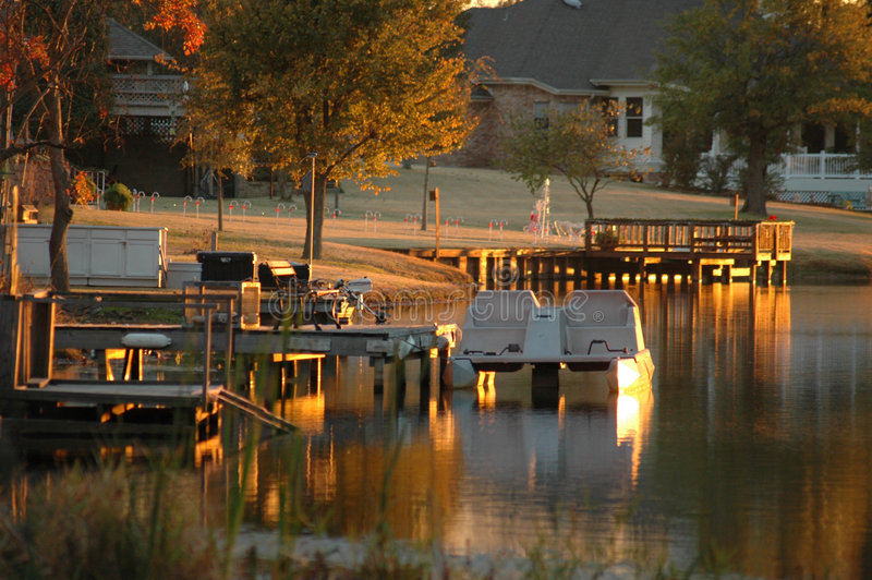 Paddle Boat. Sits at the end of dock on lake front property as the sun sets stock images
