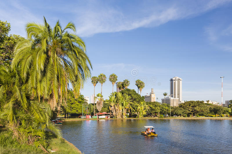 Paddle Boat in Uhuru Park In Nairobi, Kenya, editorial. NAIROBI - DECEMBER 24: People in a paddle boat on the lake of Uhuru Park in front of the skyline of royalty free stock photo