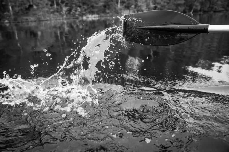 Paddle of a boat with water splashes. In black and white royalty free stock photo