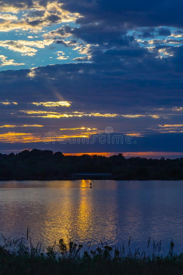 Sunset with beautiful skyline over lake Zorinsky Omaha Nebraska. Paddle canoe on lake with Sunset with beautiful clouds in the sky and lake with golden sun royalty free stock images
