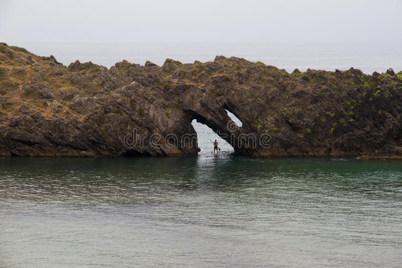 Paddle surf 1. Paddle Surf paddler crossing a rock arch on the seashore. Asturias. Spain stock images