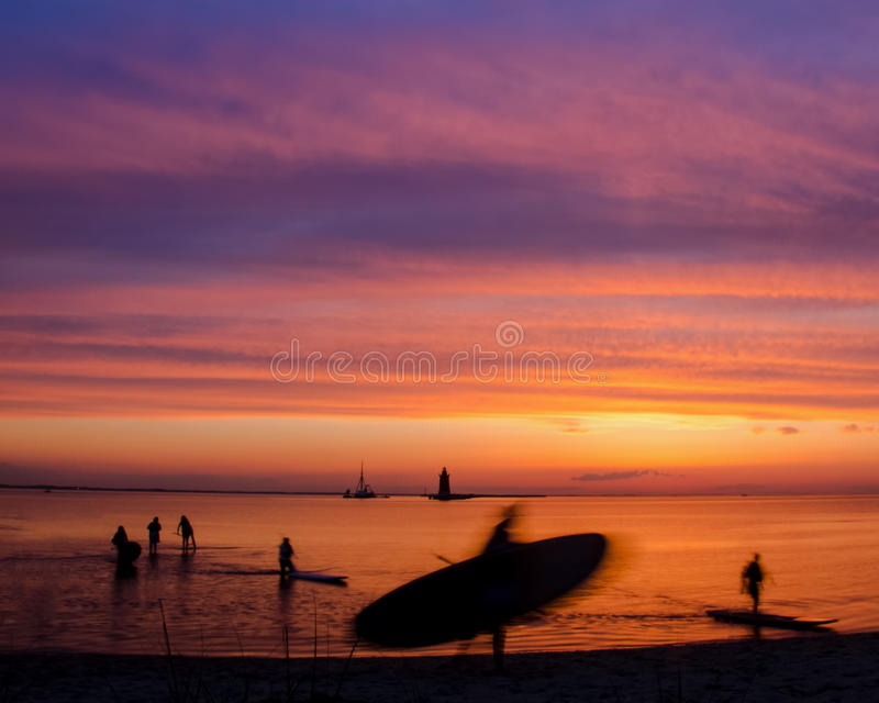 Paddle Surfers in the Sunset. Paddle surfers approaching the beach of Cape Henlopen State Park located in Lewes Delaware stock photo