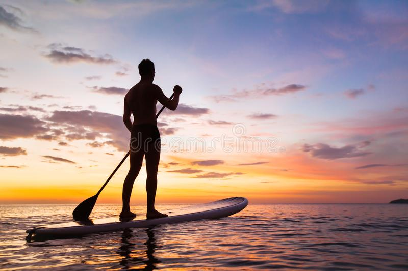 Paddleboard on the beach at sunset, SUP, leisure activity. Paddleboard on the beach at sunset, paddle standing in Thailand royalty free stock images
