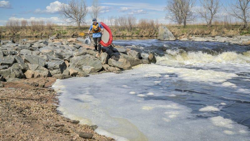 Paddleboard portaging do Paddler sobre o rio rápido fotos de stock
