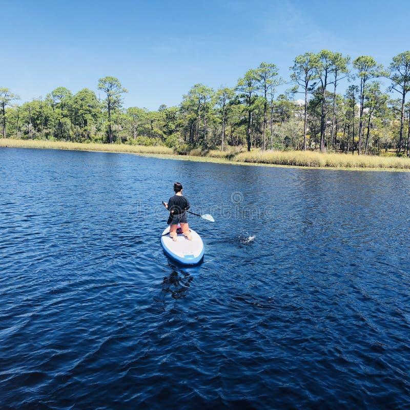 Paddleboarder i vattenfärgsemesterort arkivbilder