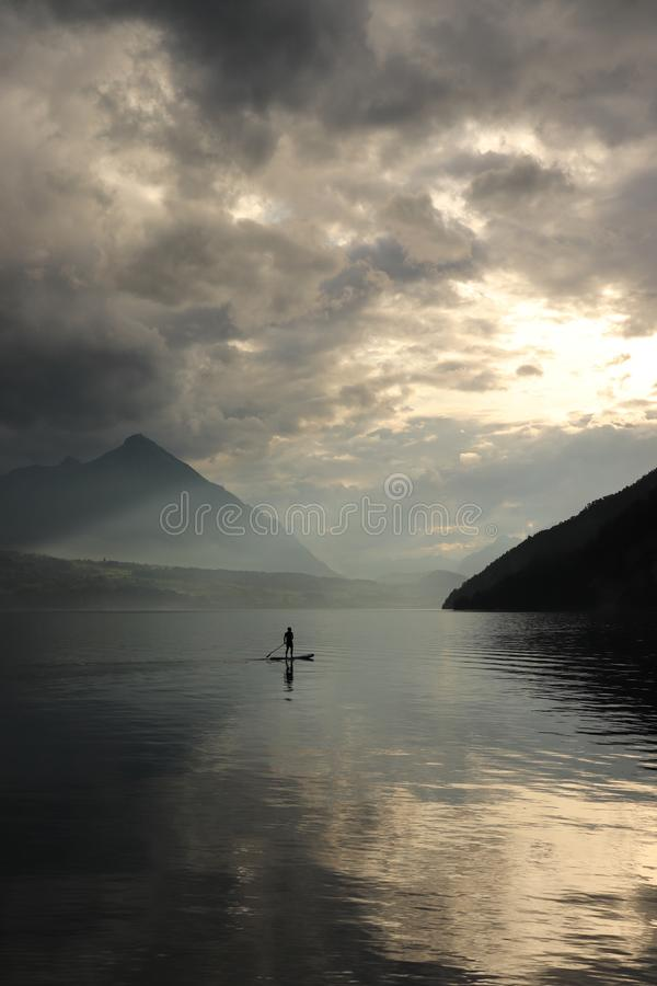 Paddleboarder on a mountian lake after storm royalty free stock photos