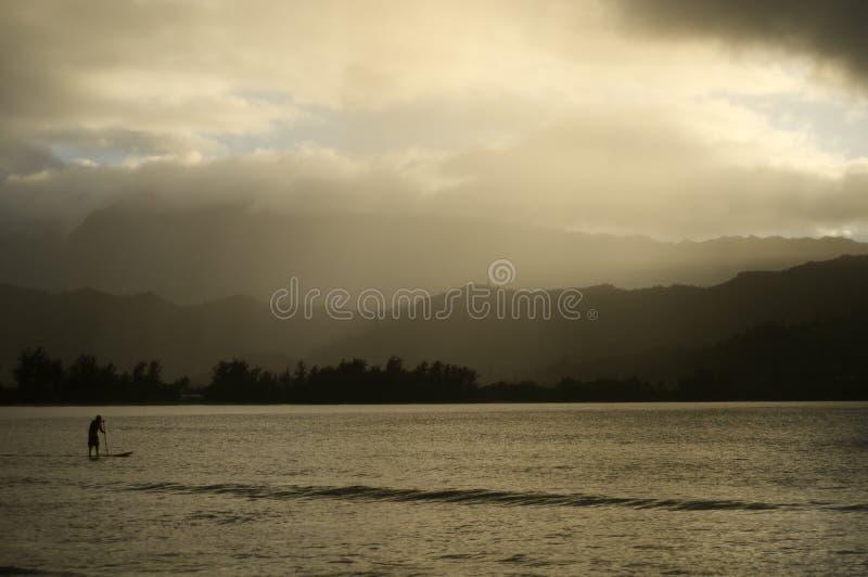 paddleboarding在朦胧的下午的夏威夷的人 库存照片