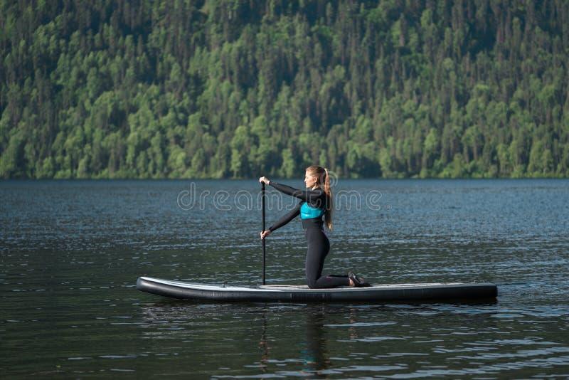 paddleboarding在膝盖的微笑的妇女在山湖 免版税库存图片
