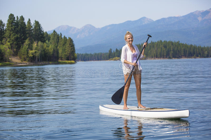 paddleboarding在风景山湖的美丽的妇女 免版税库存图片