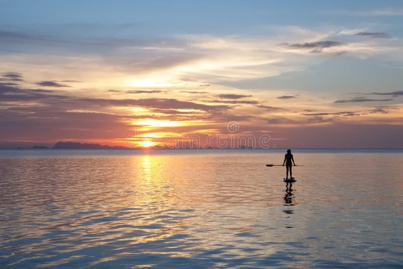 Paddleboarding au coucher du soleil photographie stock libre de droits