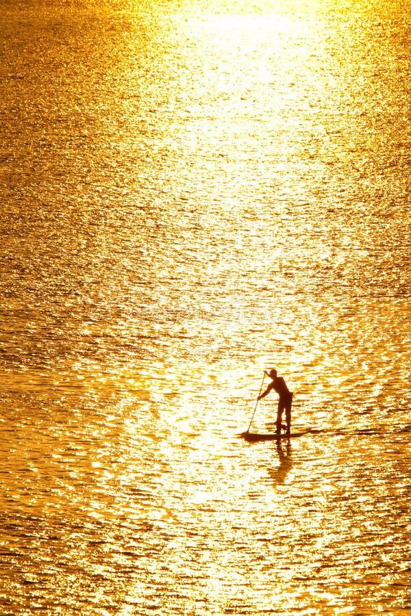 Paddleboarding dans le coucher du soleil photo libre de droits