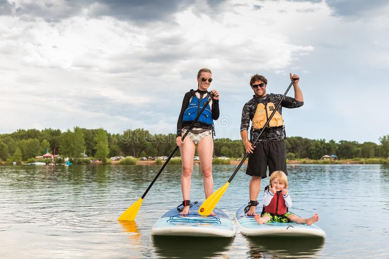 Paddleboarding. Denver, Colorado, USA-July 23, 2016. Family paddleboarding on small pond stock photography