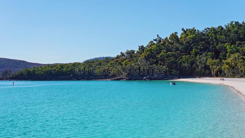 Paddler και βάρκα στο μπλε νερό μιας άσπρης παραλίας άμμου πυριτίου σε Whitsundays Αυστραλία στοκ εικόνα