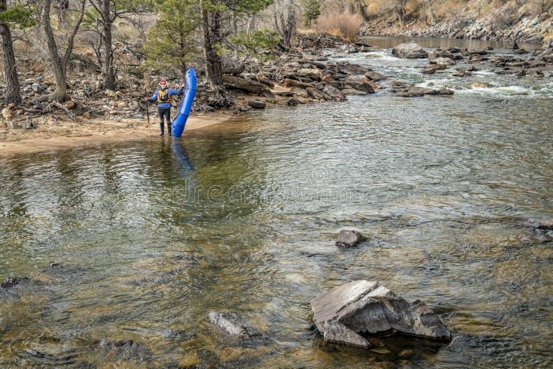 Paddler com packraft no rio da montanha imagem de stock
