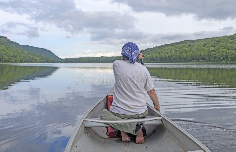 Paddler descalço em um lago calmo foto de stock