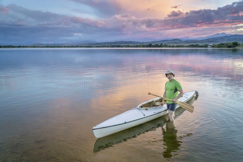 Paddler e canoa no crepúsculo fotos de stock royalty free