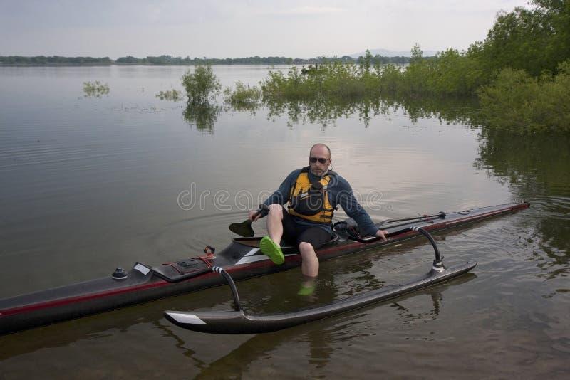 Paddler maduro em competir a canoa de guiga foto de stock
