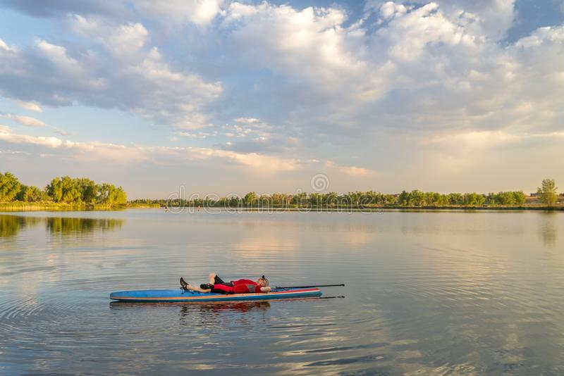 Paddler masculino que descansa em um paddleboard imagens de stock royalty free