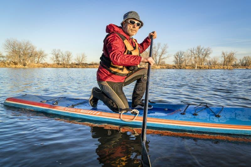 Paddler masculino superior em um suporte acima da placa de pá, foto de stock royalty free