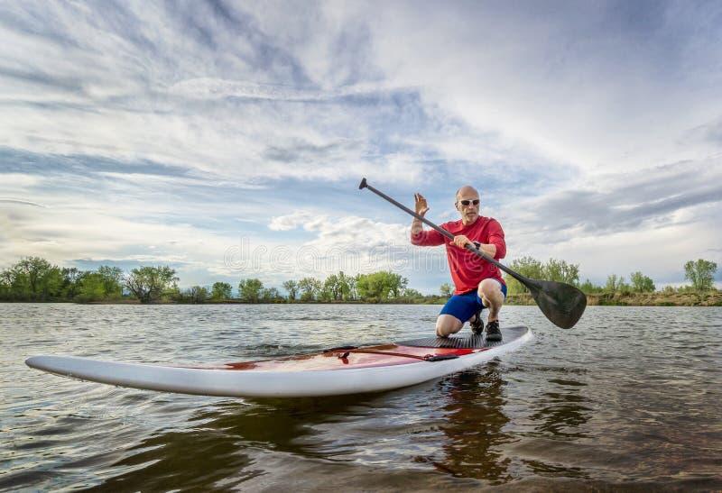 Paddler masculino superior no paddleboard do SUP fotografia de stock