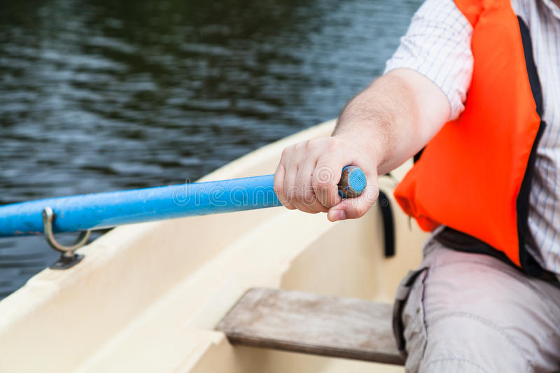 Paddler with oar on boat during water walk. Paddler in life jacket with oar on boat during water walk stock photos
