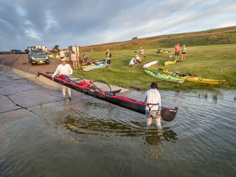Paddlers que lanzan los barcos para la raza del río fotografía de archivo libre de regalías