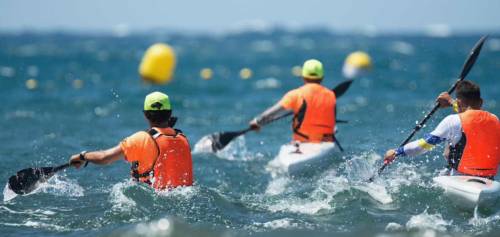 Paddlers race their ocean kayak stock images